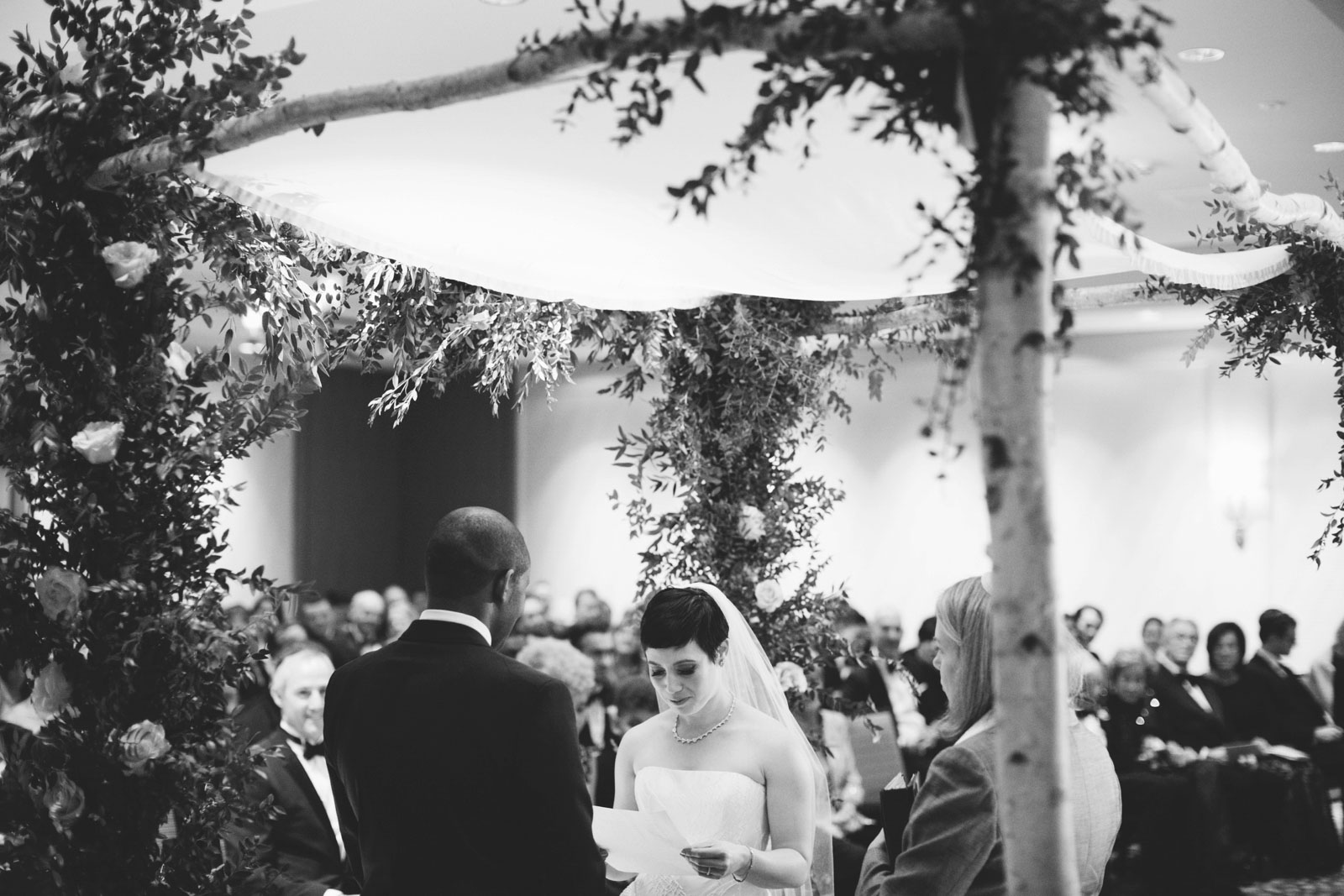 bride reading her vows under chuppah made of birch branches and greenery