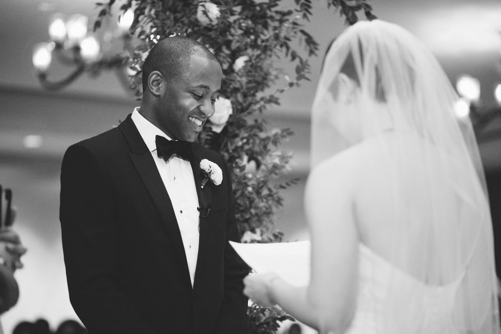 black and white shot of groom laughing while bride says her vows under chuppah