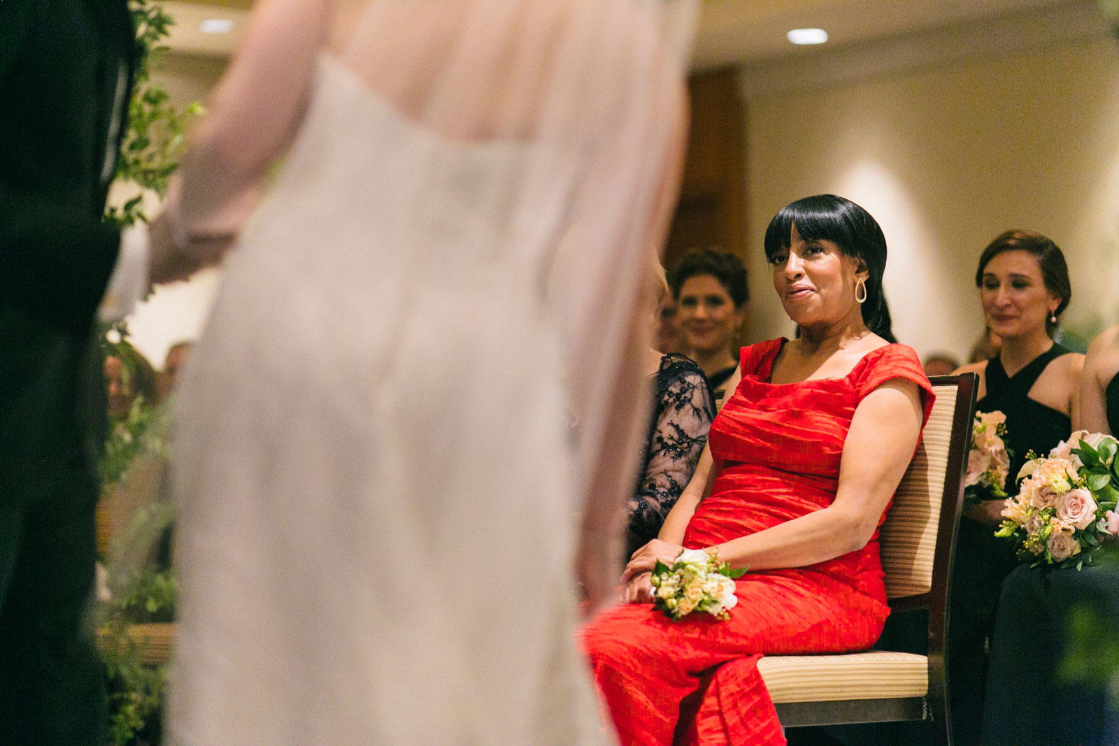 groom's mother smiles as she watches her son's emotional wedding ceremony