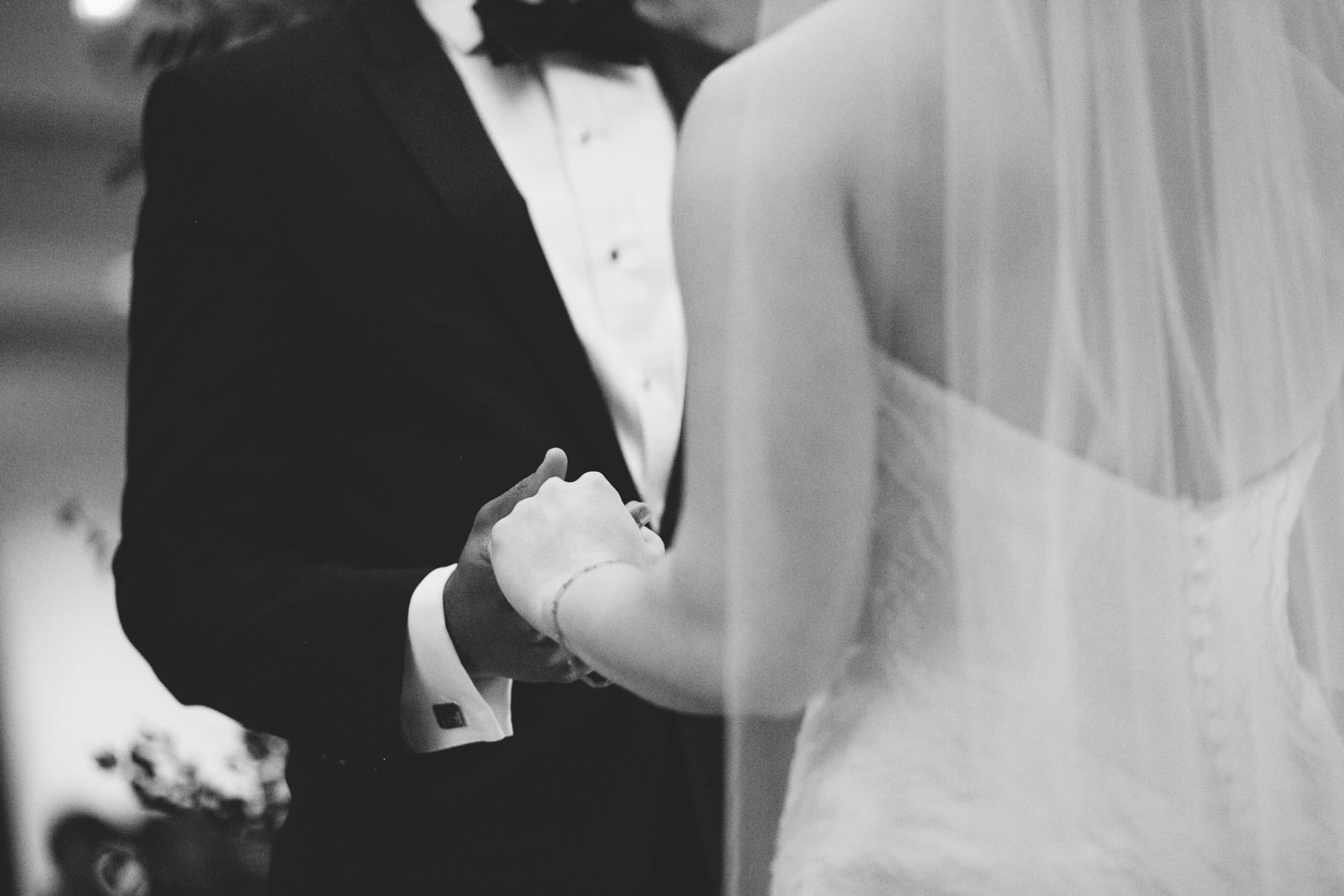 black and white close up shot of bride and groom holding hands during their emotional ceremony