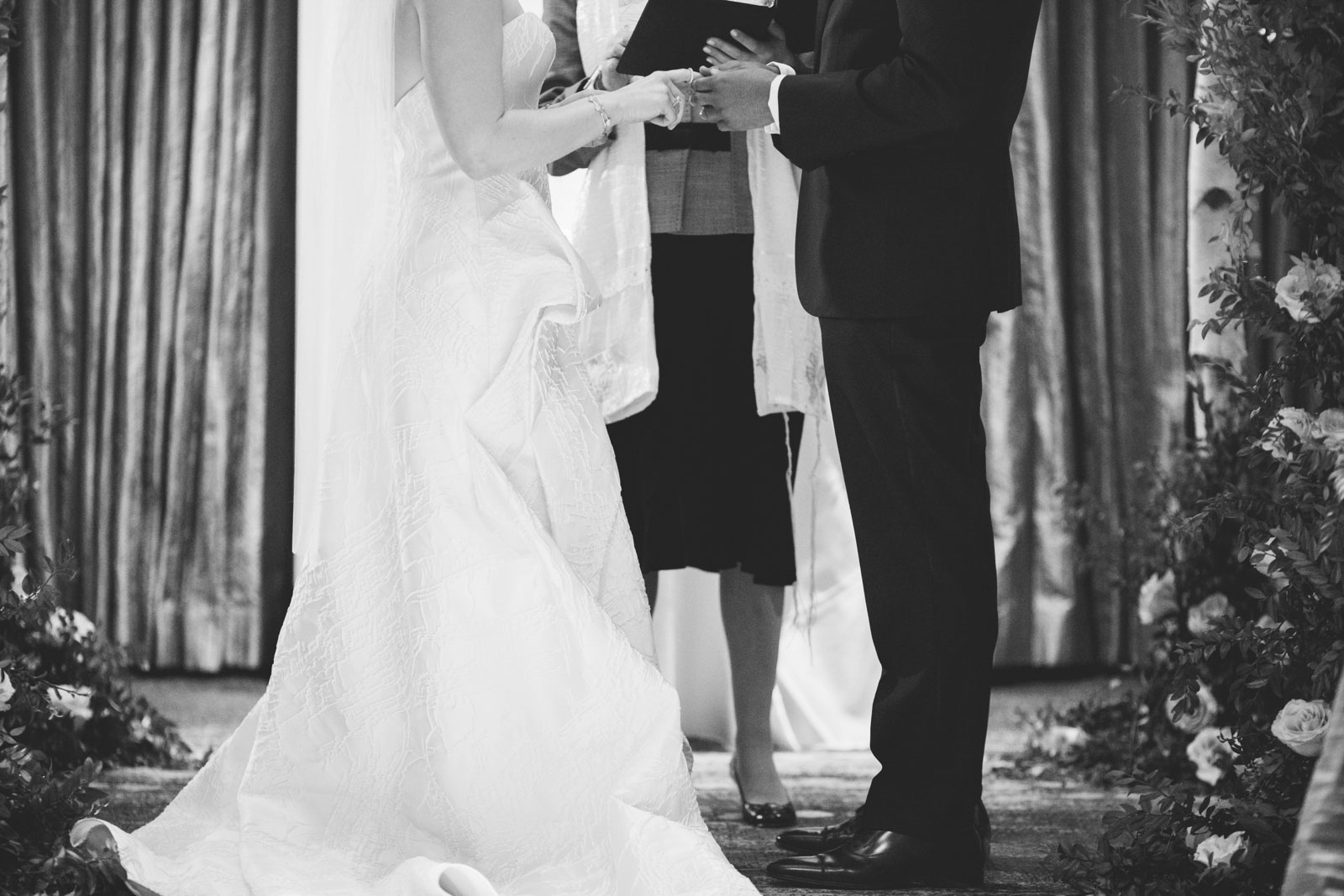 black and white shot of bride and groom exchanging rings during multicultural wedding ceremony