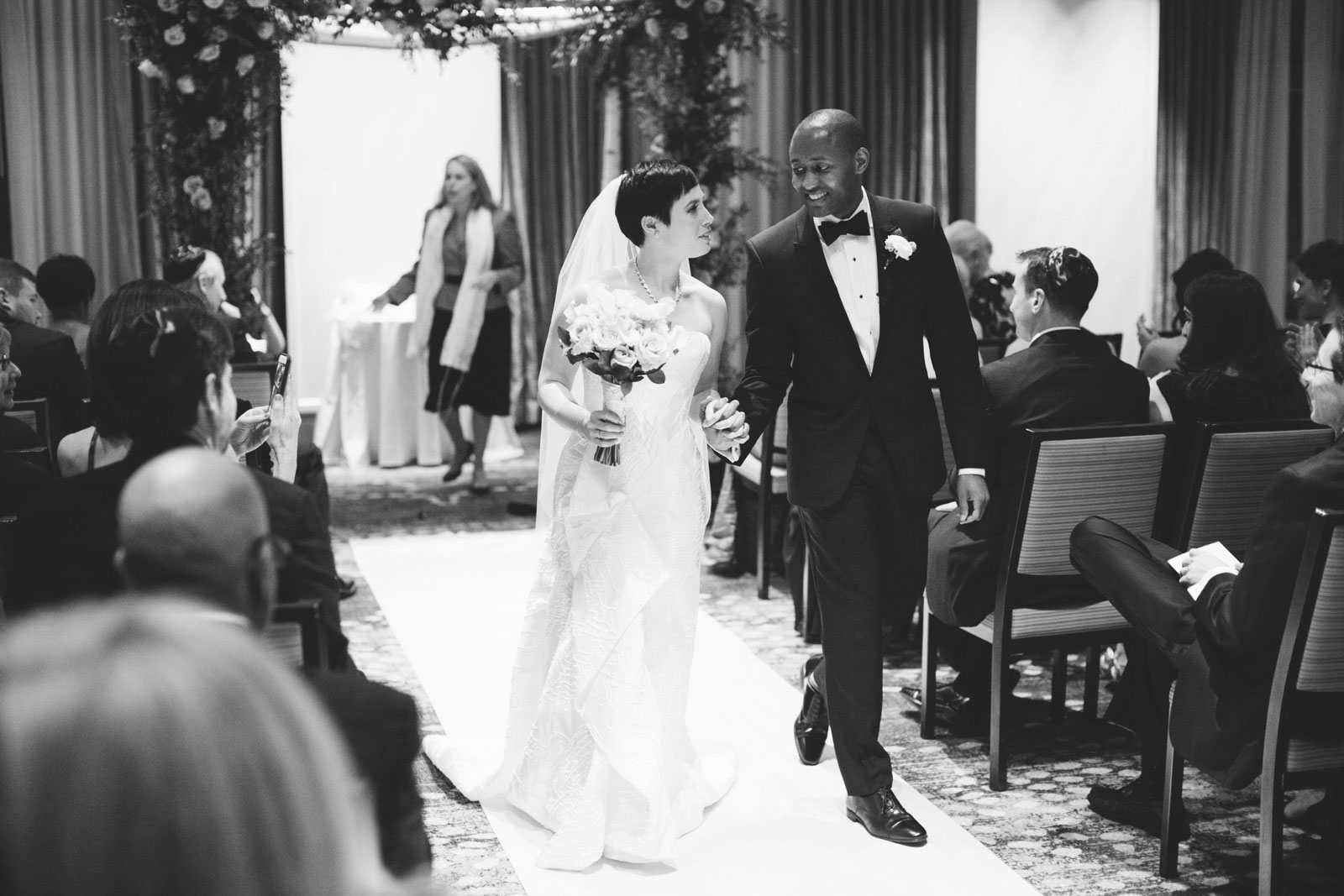 bride and groom walking back down the aisle together after their interracial wedding ceremony