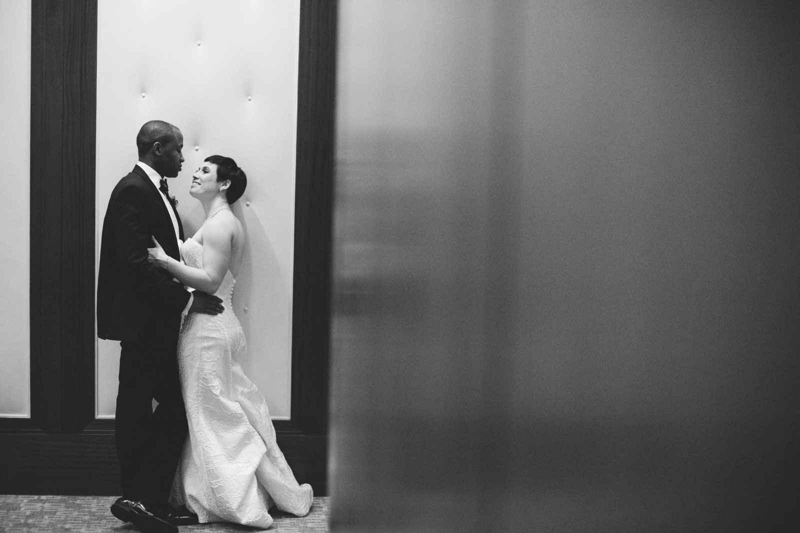 Black and white portrait of bride and groom holding each other close after their interracial wedding
