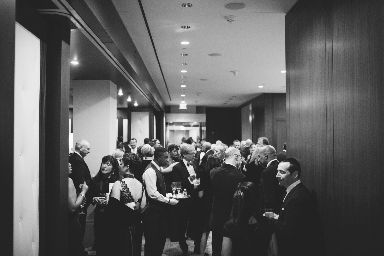 Black and white candid of guests mingling during cocktail hour at the Ritz-Carlton Boston
