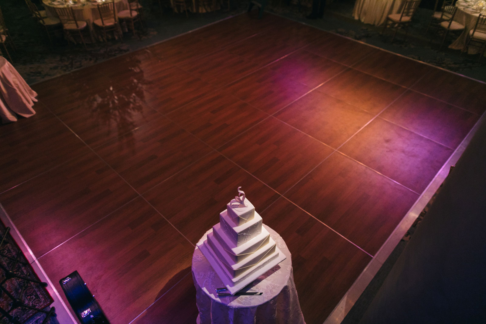 Shot of the dance floor from above with romantic lighting and square multi-tiered wedding cake