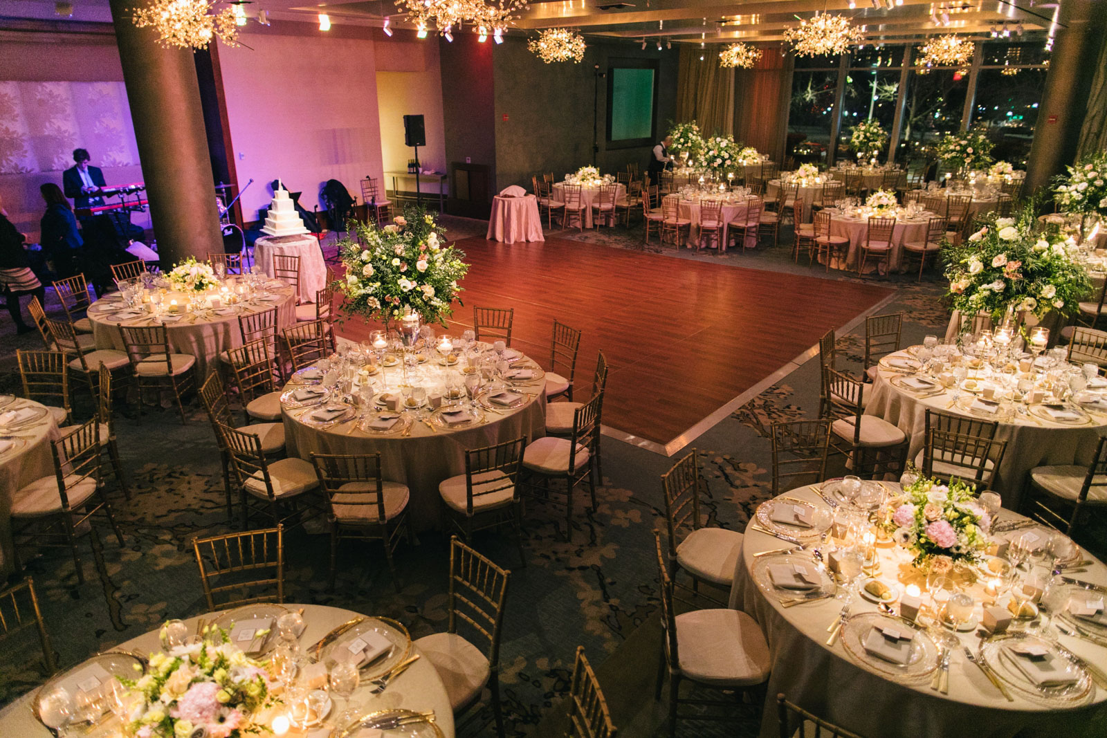 Room shot of romantic wedding reception ballroom at Ritz-Carlton with modern crystal chandeliers