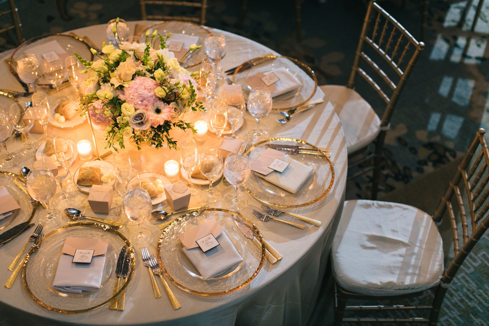 Modern Tablescape with pastel floral centerpiece, gold-rimmed dishes, and warm candle light