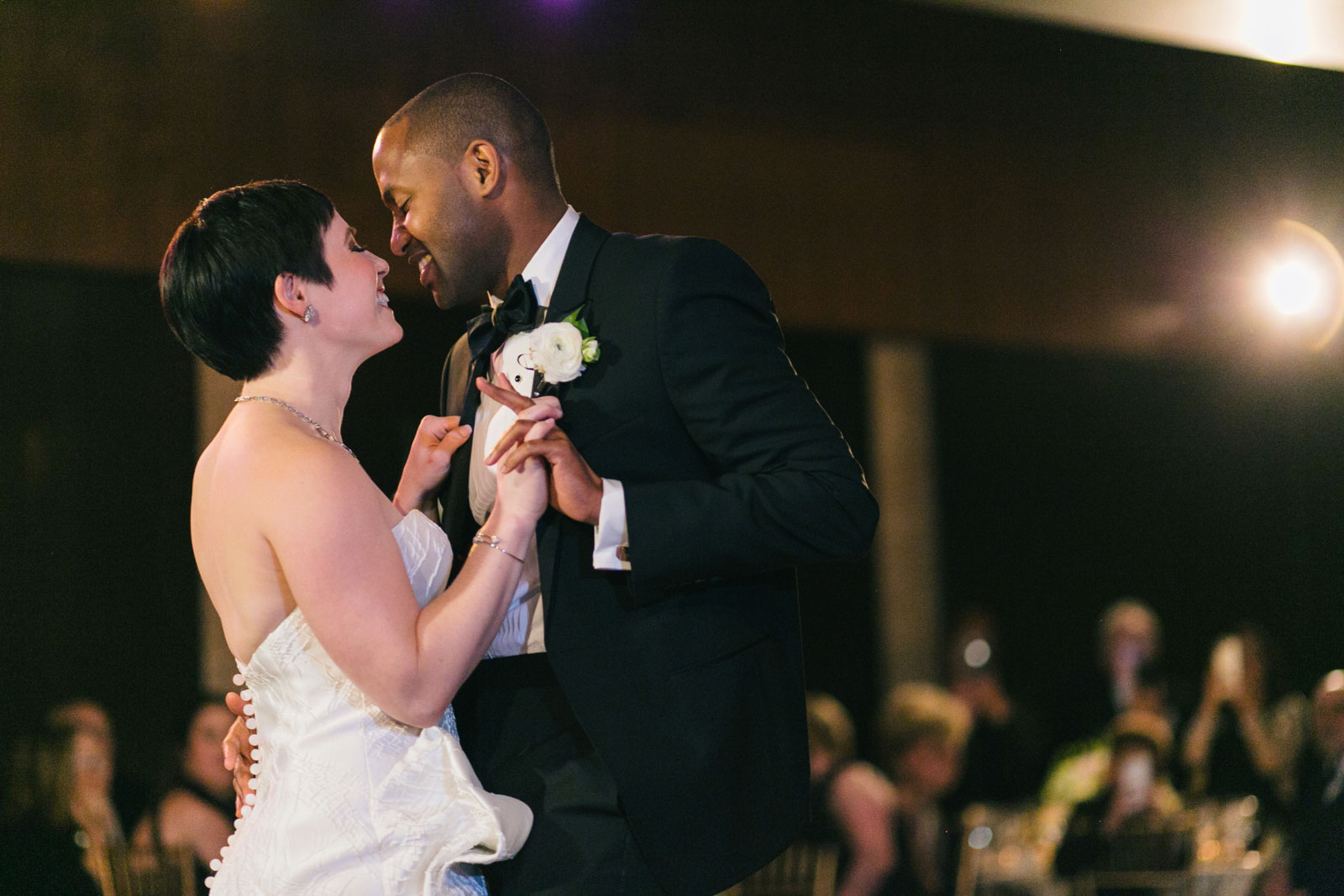 Couple smiling and pulling each other in close during their first dance at black tie wedding Boston