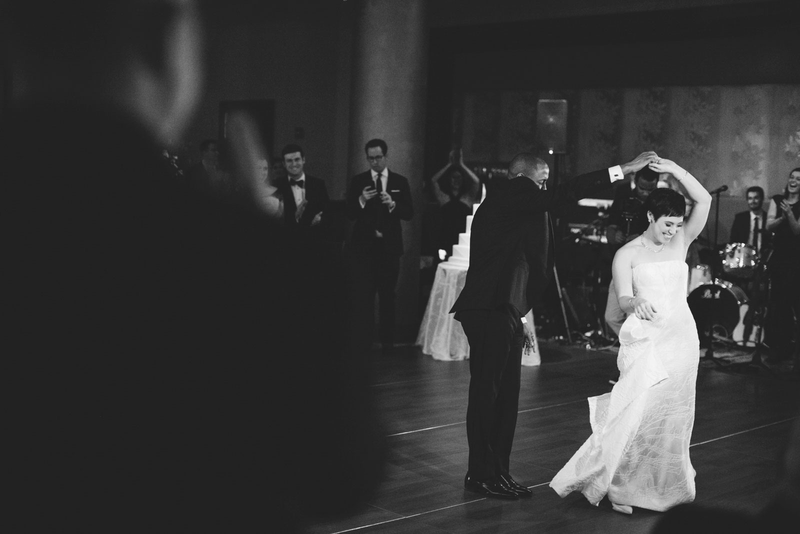Black and white shot through crowd of groom spinning bride during their fun first dance