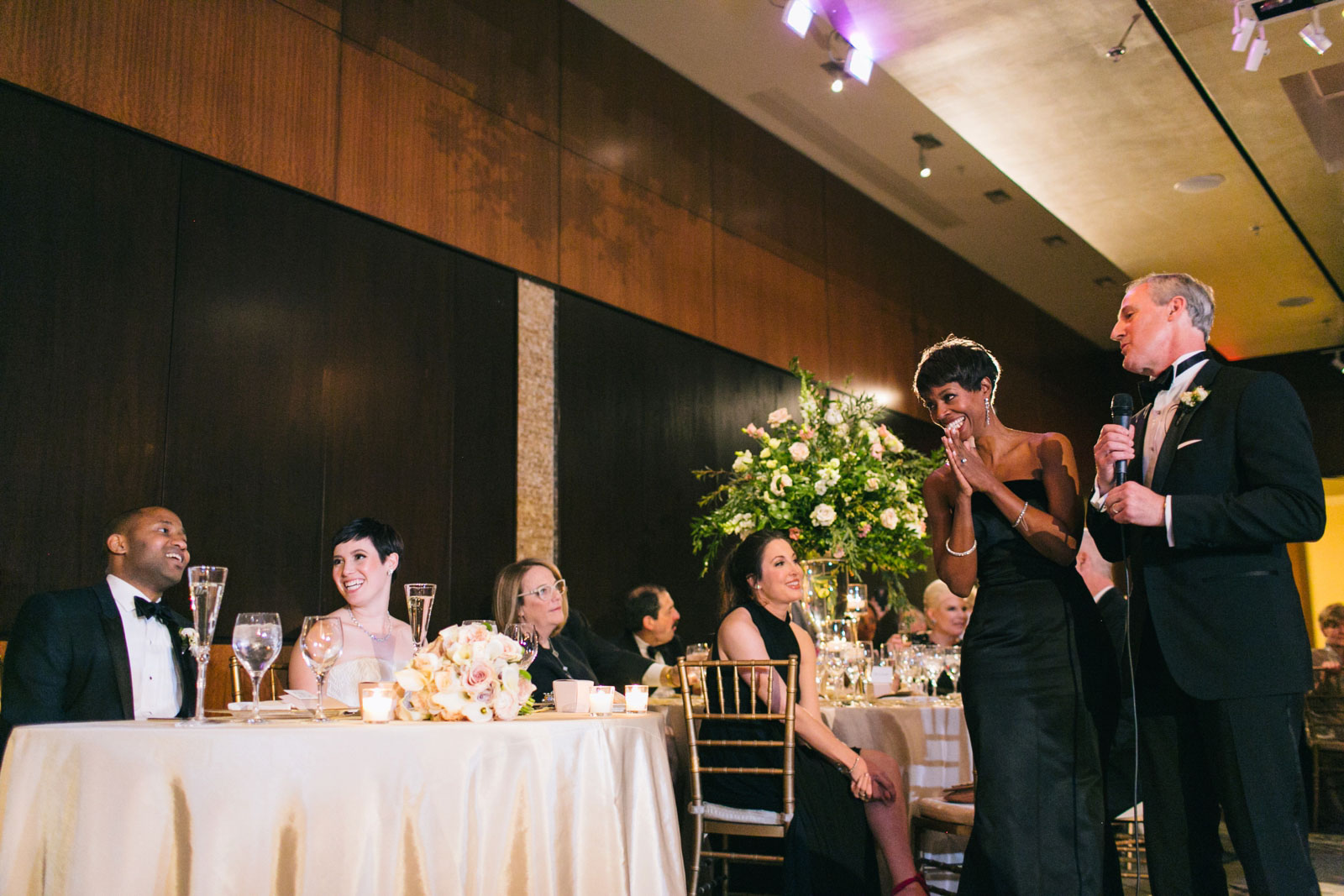 Bride and groom laugh as parents of the bride give welcome speech at interracial modern wedding