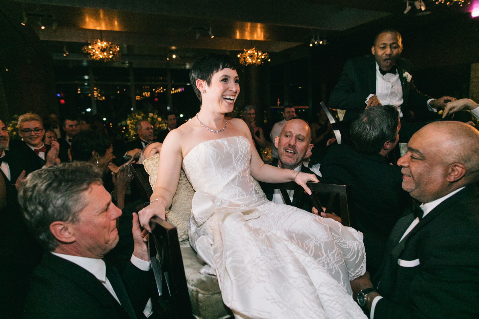 Bride and groom laugh as they are lifted up in chairs during Hora at multicultural wedding reception