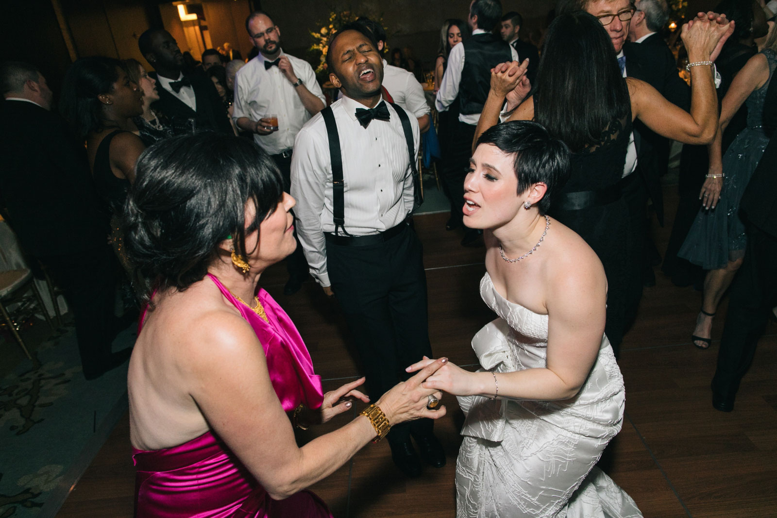 Bride and groom having fun on the dance floor during their interracial wedding reception