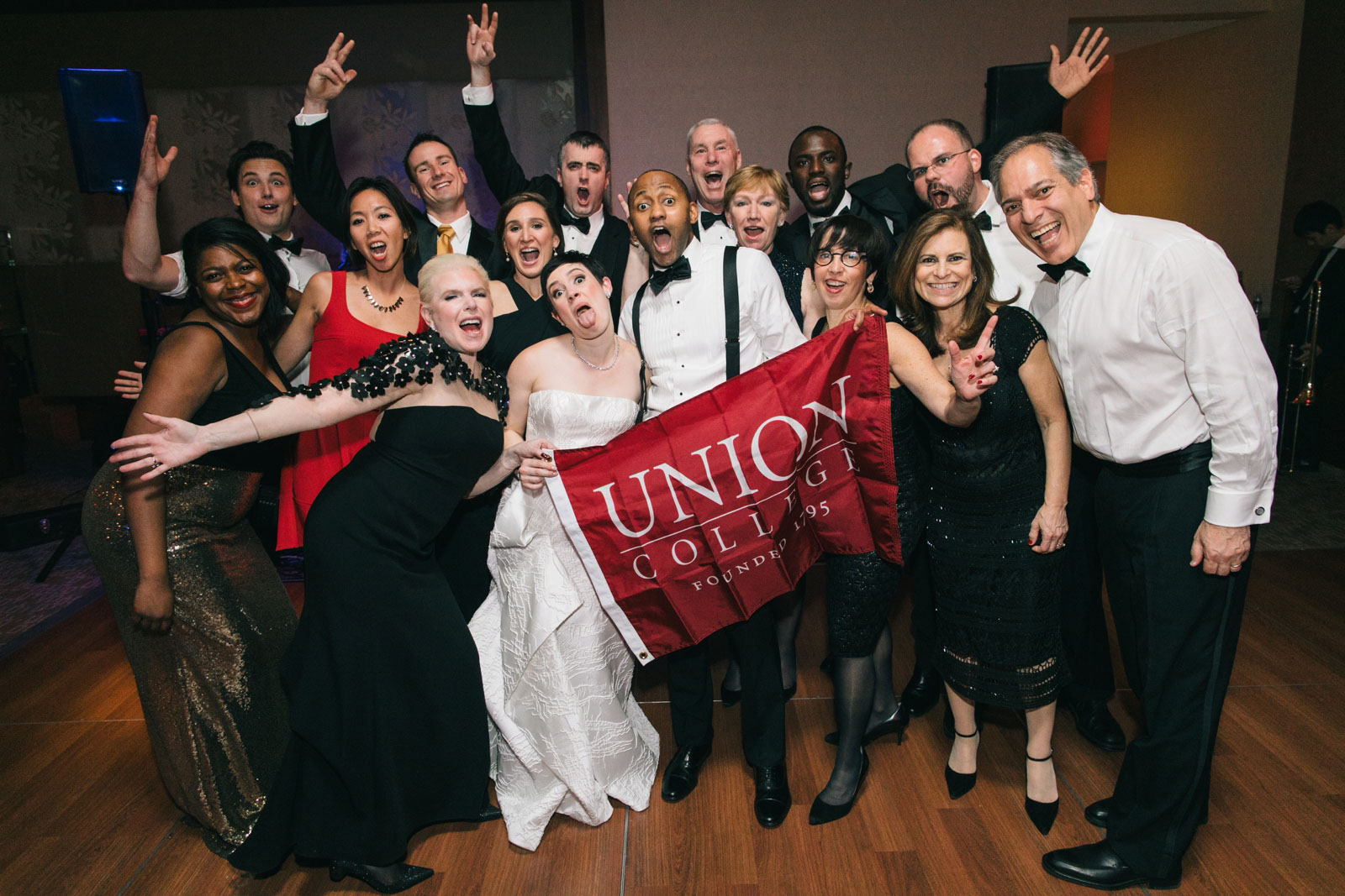 Bride and groom and wedding guests doing a silly pose holding Union college flag