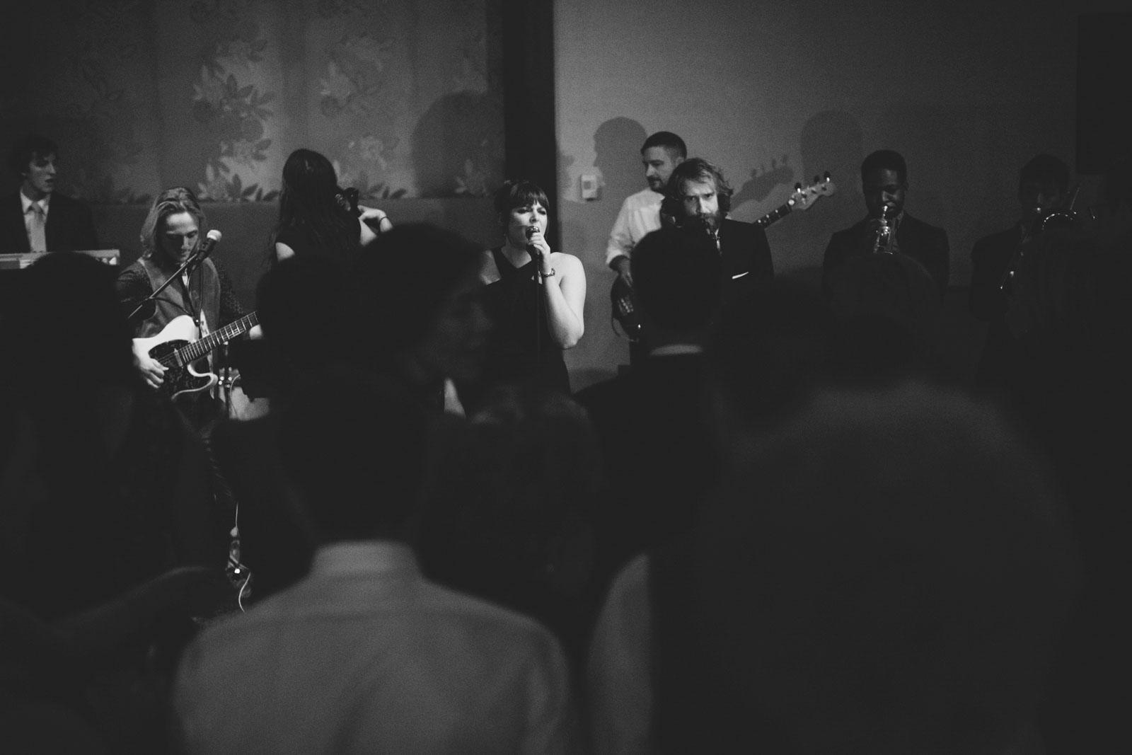 Dramatic black and white shot of maid of honor surprising bride by singing during reception