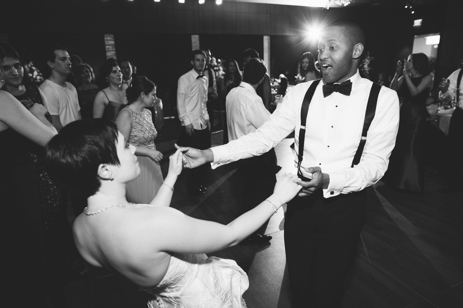 Black and white dance floor shot, bride and groom dancing together at interracial wedding reception