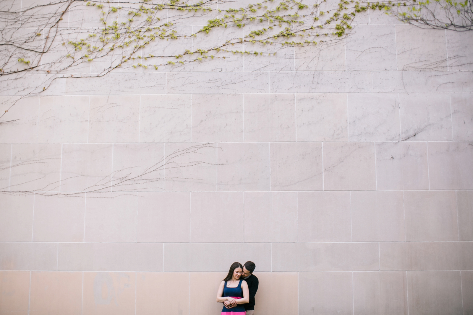 Romantic engagement portrait of couple standing in front of Wellesley building with ivy on wall.