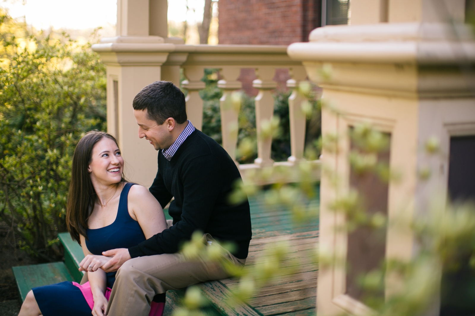 Casual engagement portraits of couple sitting on stoop and laughing together at Wellesley college.