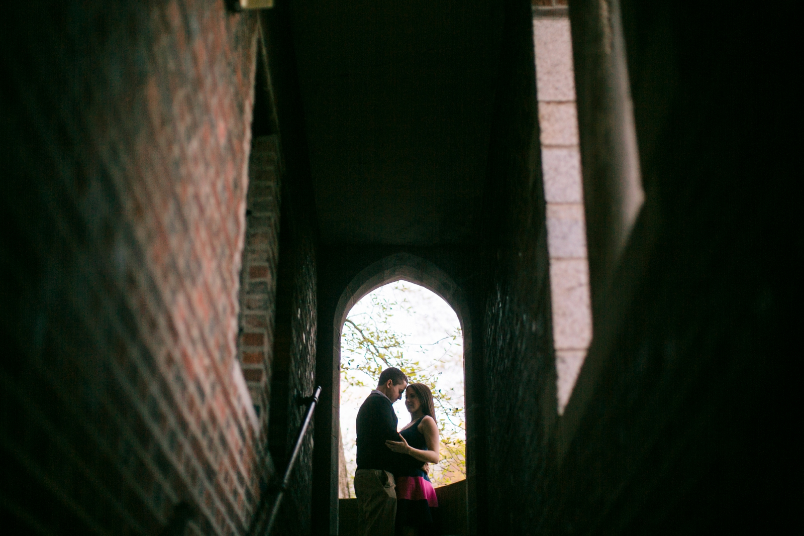 Silhouette of couple pulling each other in close, romantic moody engagement portrait